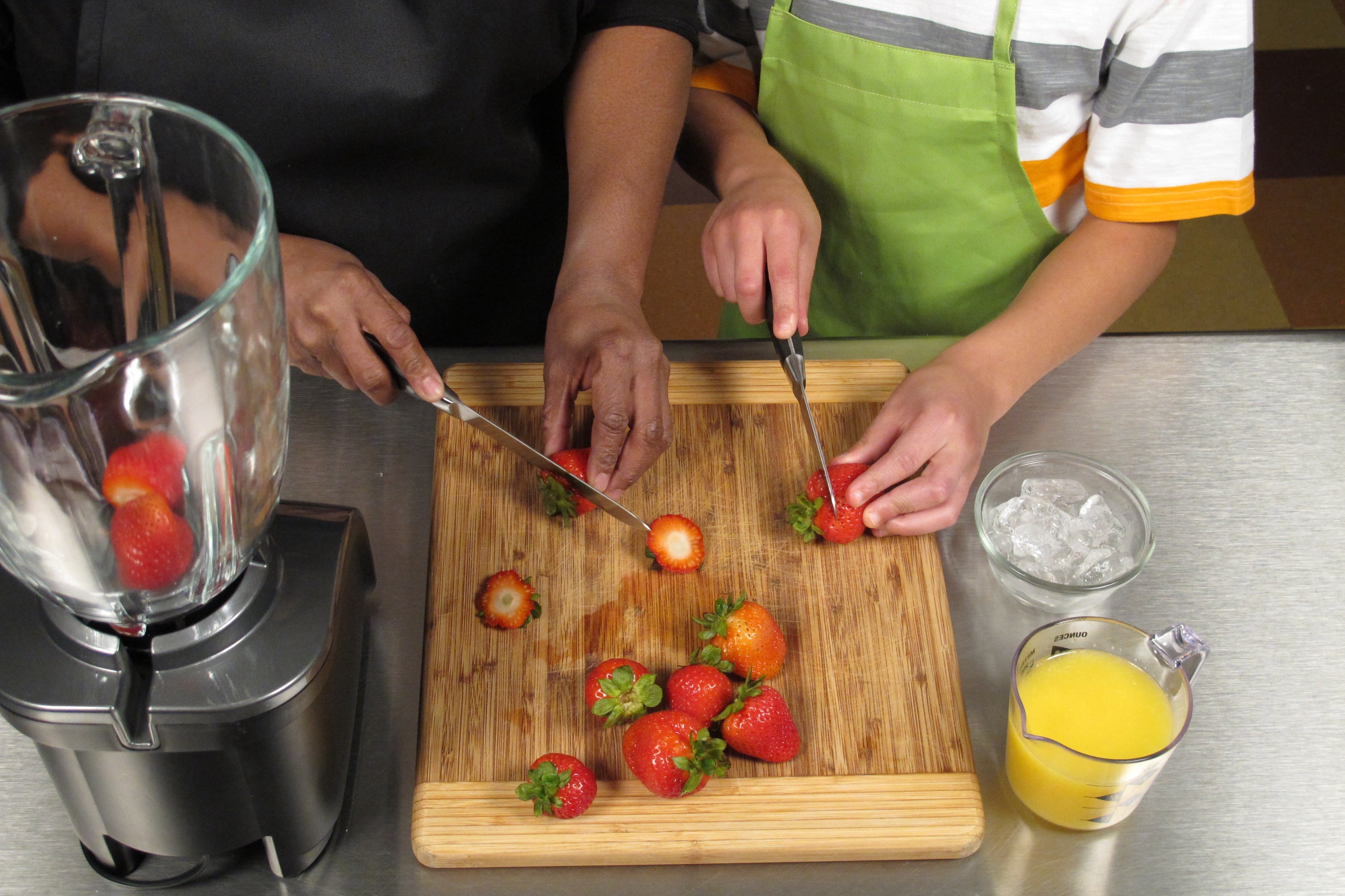 Remove stem and leaves and cut strawberries in half. Younger children can use a plastic knife for this step if desired.