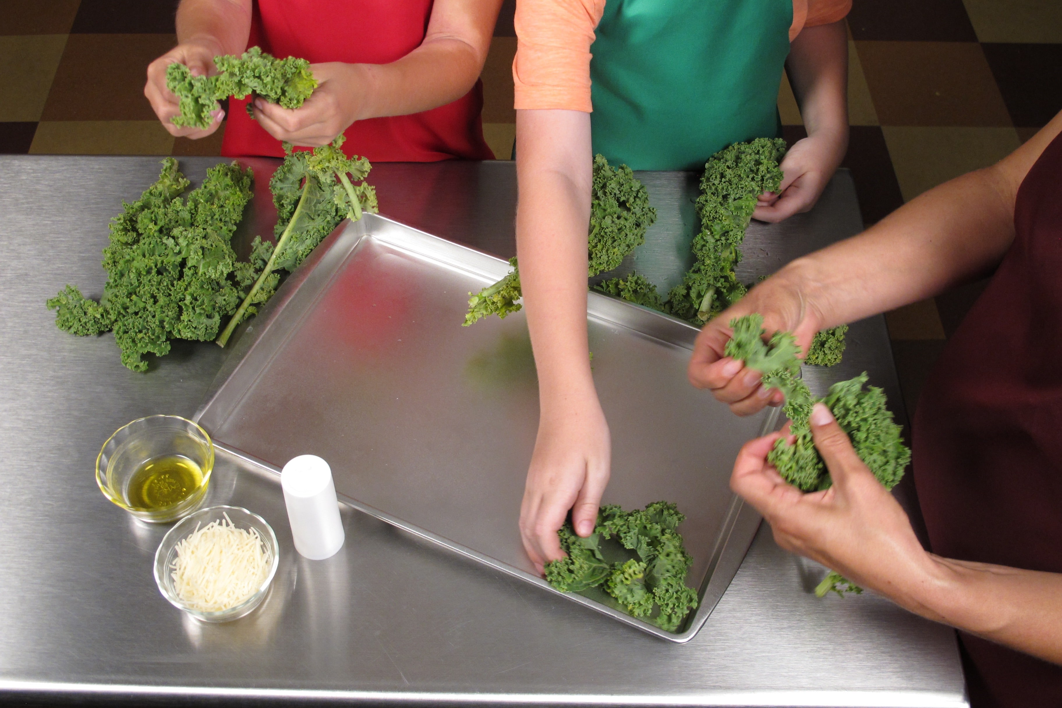 Carefully tear kale leaves from the thick stem. Tear into bite-sized pieces and place on baking sheet.